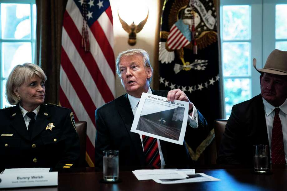 "President Donald Trump holds up a photo of a ""typical standard wall design"" as he speaks during a roundtable discussion on border security with administration officials at the White House on Friday. Photo: Washington Post Photo By Jabin Botsford / The Washington Post"