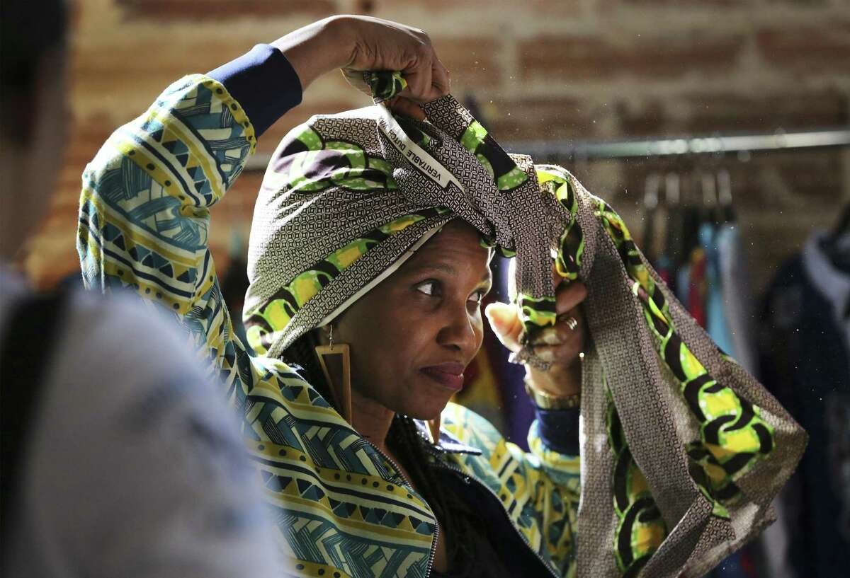 Unyime Udosen shows how to wrap and wear a head tie at her vendor's booth at the Olaju African Market Creative Arts Festival which showcases arts from the African continent at the Blue Star Arts Complex on Saturday, Jan. 12, 2019. As one of the officially recognized events of DreamWeek which promotes the teachings of Dr. Martin Luther King, the Olaju Festival provides enlightenment of African art and culture to San Antonio. (Kin Man Hui/San Antonio Express-News)