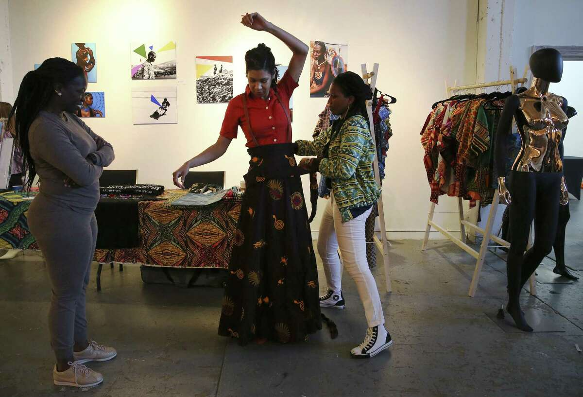 Helen Holmes (center) gets assistance trying on an Ankara skirt from Unyime Udosen (right) at the Olaju African Market Creative Arts Festival which showcases arts from the African continent at the Blue Star Arts Complex on Saturday, Jan. 12, 2019. As one of the officially recognized events of DreamWeek which promotes the teachings of Dr. Martin Luther King, the Olaju Festival provides enlightenment of African art and culture to San Antonio. (Kin Man Hui/San Antonio Express-News)