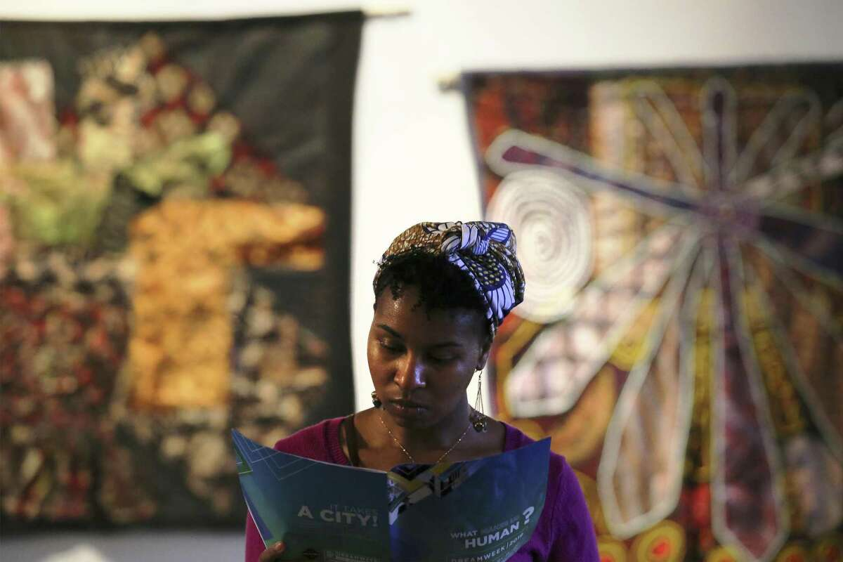 Selena Mitchell stands near an exhibit of textile-based art known as Bitik at the Olaju African Market Creative Arts Festival which showcases arts from the African continent at the Blue Star Arts Complex on Saturday, Jan. 12, 2019. As one of the officially recognized events of DreamWeek which promotes the teachings of Dr. Martin Luther King, the Olaju Festival provides enlightenment of African art and culture to San Antonio. (Kin Man Hui/San Antonio Express-News)
