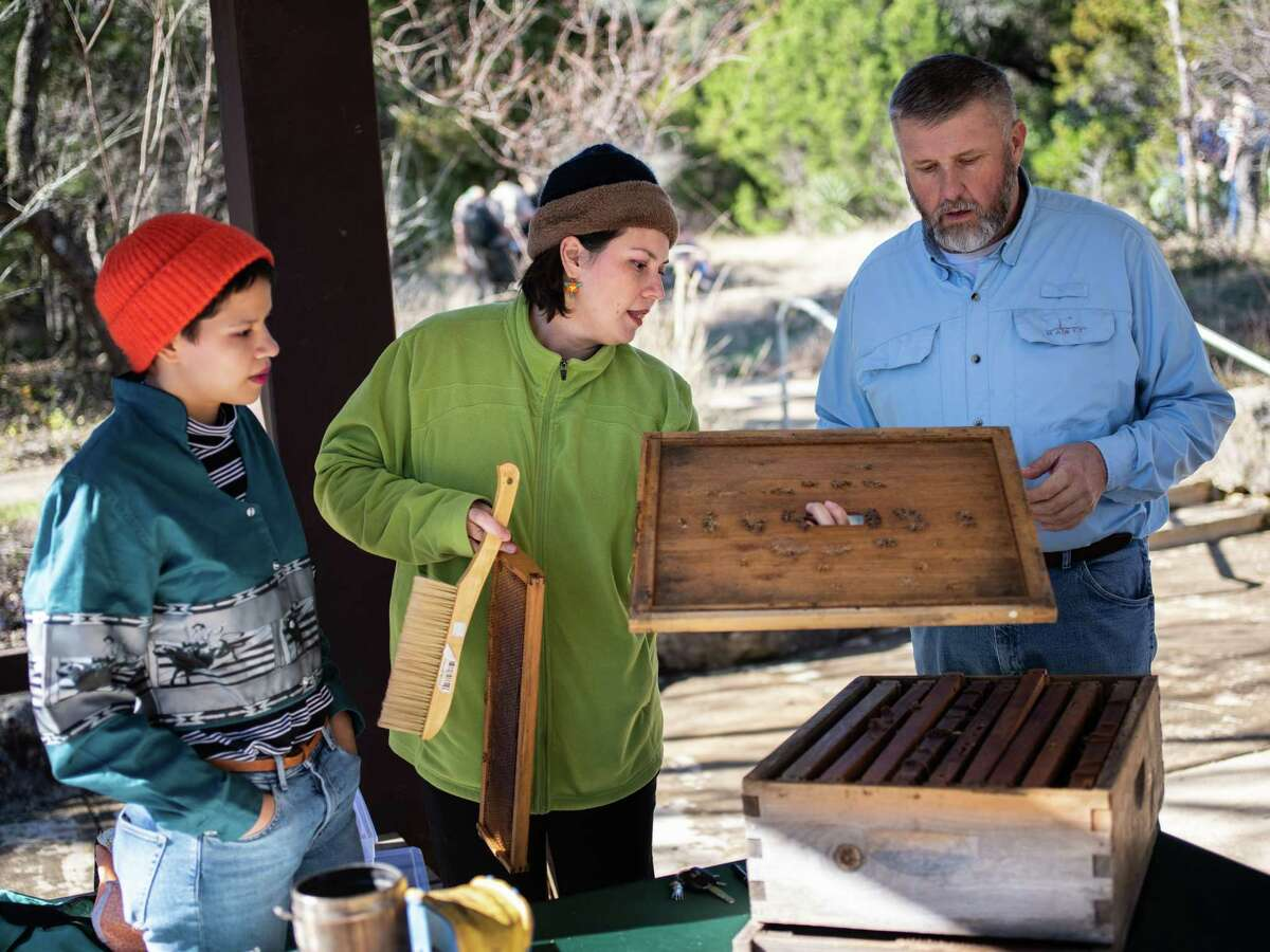 Laura Salazar, center, describes a super's layout, which consists of 8-10 frames where bees create their wax honeycombs, to Ned Pyatt, right, during an informational exhibition put on by Salazar of Honey Love Bee Removal at Friedrich Wilderness Park on Saturday, January 12, 2019. Joaquina Salazar, Laura's daughter, works with the business as well when she's not at school in Connecticut.