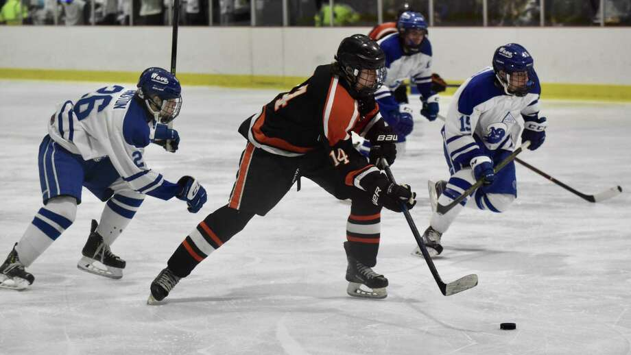 Ridgefield's Will Forrest (14) gets in front of Darien's Luke Johnston (26) and John Reid (19) during a boys hockey game at the Darien Ice House on Saturday. Photo: Dave Stewart / Hearst Connecticut Media