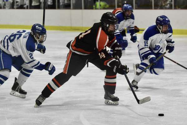 Ridgefield's Will Forrest (14) gets in front of Darien's Luke Johnston (26) and John Reid (19) during a boys hockey game at the Darien Ice House on Saturday.