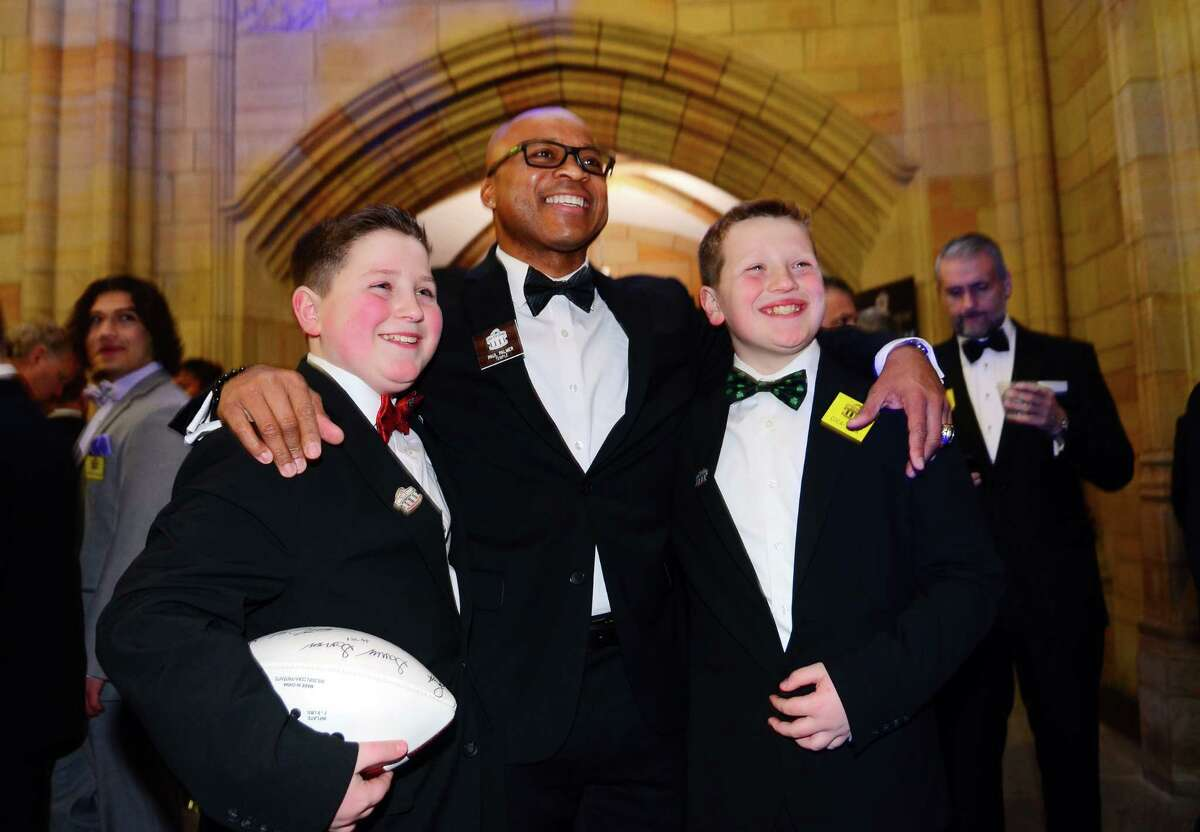 Benjamin Flaherty, 13, left, and his little brother Connor, 11, of Bedford, Hew Hampshire, pose for photos with Paul Palmer of Temple during the 52nd annual Walter Camp All-Americans black tie Awards Dinner at Yale's Lanman Center in New Haven, Conn., on Saturday Jan. 12, 2019.
