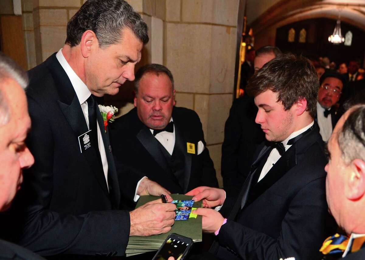 Vince Camera, of Fairfield, at right, gets an autograph from former NFL playerand ESPN host Mike Golic during the 52nd annual Walter Camp All-Americans black tie Awards Dinner at Yale's Lanman Center in New Haven, Conn., on Saturday Jan. 12, 2019.