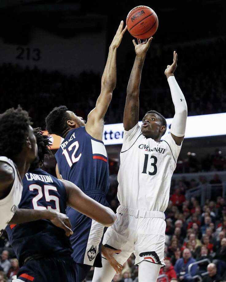 Cincinnati's Tre Scott shoots over Connecticut's Tyler Polley during Saturday's gamein Cincinnati. Photo: John Minchillo / Associated Press / Copyright 2019 The Associated Press. All rights reserved.