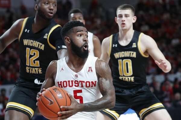 Houston Cougars guard Corey Davis Jr. (5) spins around as he fought off Wichita State Shockers forward Morris Udeze (12) and guard Erik Stevenson (10) during the first half of an NCAA Men's basketball game at Fertitta Center, Saturday, Jan. 12, 2019, in Houston.