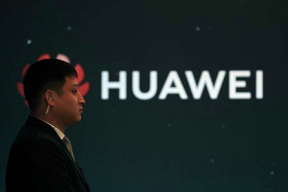 """In this Jan. 9, 2019, photo, a security guard stands near the Huawei company logo during a new product launching event in Beijing. The Chinese Foreign Ministry said late Friday, Jan. 11, 2019, it is """"closely following the detention of Huawei employee Wang Weijing"""" on charges of allegedly spying for China, and has asked Poland to """"handle the case lawfully, fairly, properly and to effectively guarantee the legitimate rights of the person, his safety and his humanitarian treatment,"""" according to state broadcaster CCTV. (AP Photo/Andy Wong) Photo: Andy Wong / Copyright 2018 The Associated Press. All rights reserved."""