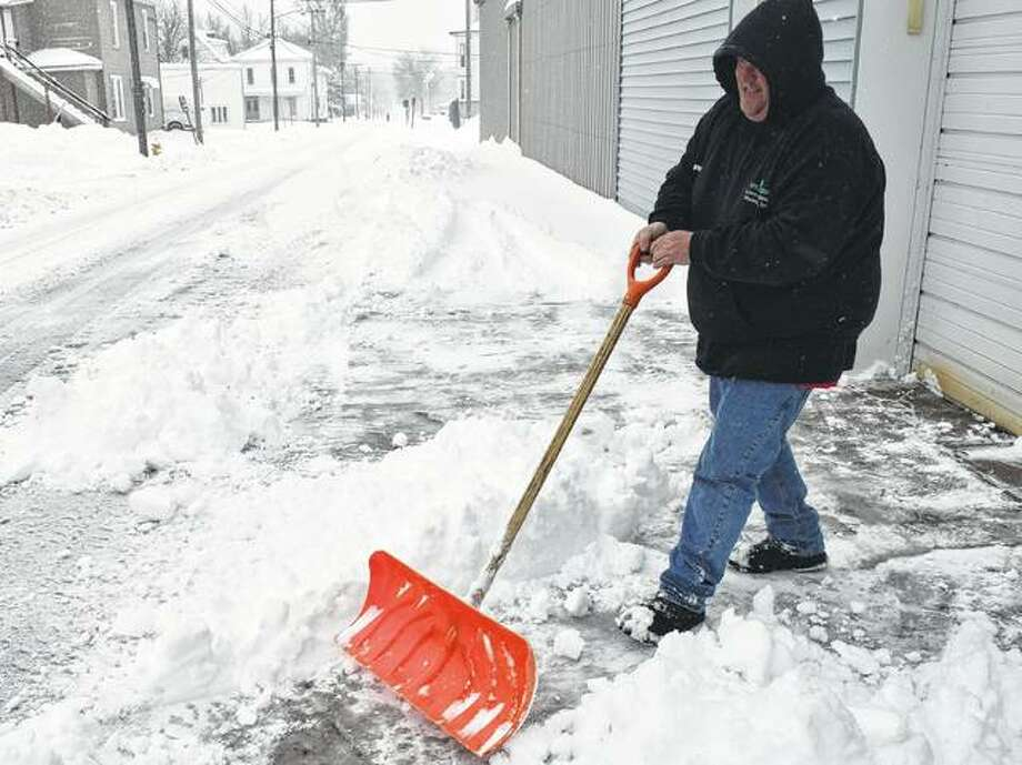 Terry Hickey with Green Works shovels snow from sidewalks Saturday in Jacksonville. Photo: Samantha McDaniel-Ogletree | Journal-Courier