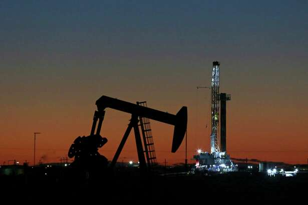 An oil rig and pump jack are at work near Midland. The oil and gas industry is in sort of a holding pattern with prices hovering around $50 a barrel.