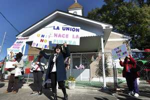 Mary Carmen Gallegos holds up signs as she organized parishioners from St. Stephen Catholic Church as they stood outside of the fenced off church before heading off to protest, Sunday, Jan. 13, 2019, in front of the Co-Cathedral because the Diocese of Galveston-Houston still hasn't announced a timeline to reopen their church in Houston.