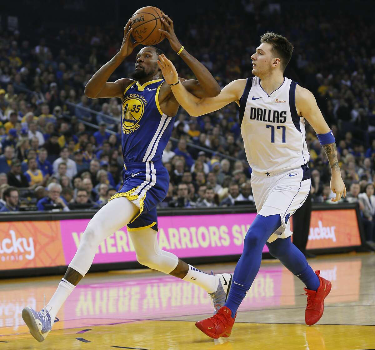 Golden State Warriors forward Kevin Durant (35) drives to the basket for a lay up against Dallas Mavericks forward Luka Doncic (77) in the first half of an NBA game at Oracle Arena on Saturday, Dec. 22, 2018, in Oakland, Calif.