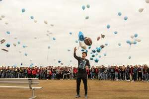 Harlan High School football player Samuel Carter center along with other students and parents release balloons at the school's football field honoring football player Shomari Anderson was killed in an auto accident on Saturday.