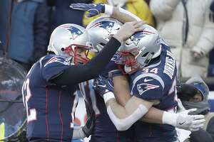 Patriots quarterback Tom Brady congratulates running back Rex Burkhead after Burkhead scored a second-quarter touchdown against the Chargers on Sunday.