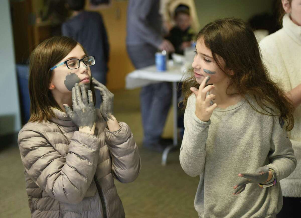 Above, Josie Friedman, left, and Madeleine Milgram, both Greenwich 9-year-olds, cleanse their face with mud, similar to what is found in the Dead Sea, during the interactive