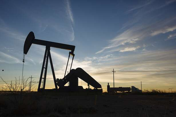 A tanker truck drives past a pump jack in the Permian Basin area of Loving County, Texas, U.S., on Saturday, Dec. 15, 2018. Once the shining star of the oil business, gasoline has turned into such a drag on profits that U.S. refiners could be forced to slow production in response. Photographer: Angus Mordant/Bloomberg