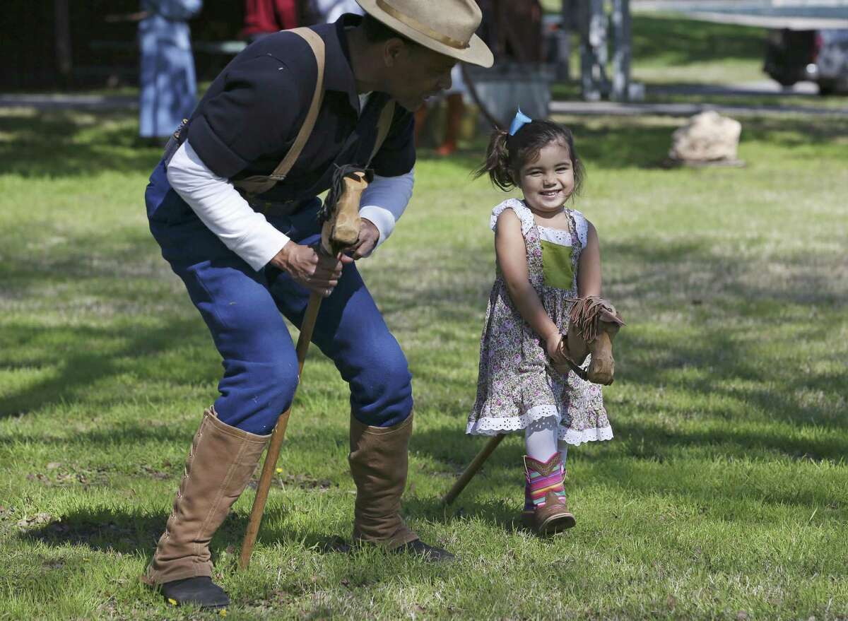 Lucy Stalcup, 2, helps round up bad guys with the help from interpreter, Allen Mack, during Buffalo Soldier Day at the University of Texas at San Antonio Institute of Texan Cultures, Sunday, Jan. 13, 2019. The event was part of DreamWeek.