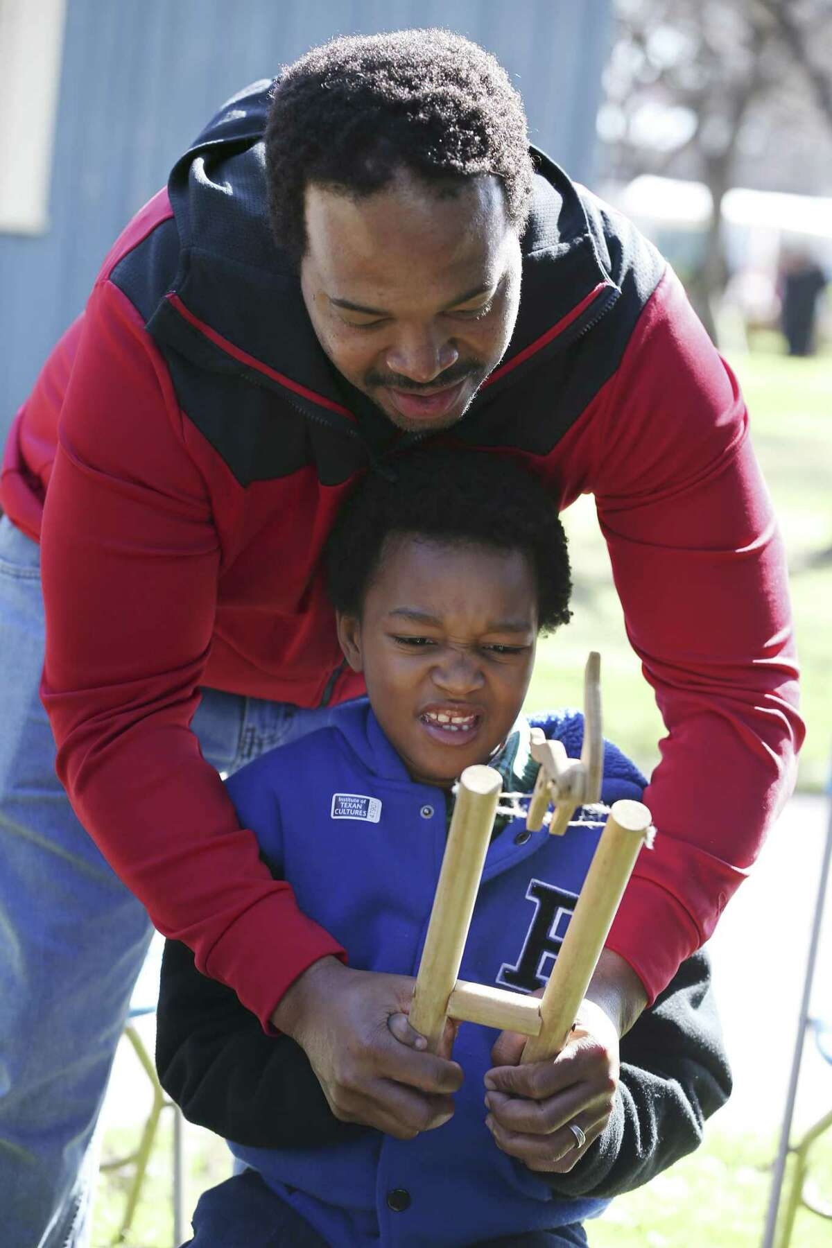 Julius William helps his son, Brennyn, 8, play with a handmade toy during Buffalo Soldier Day at the University of Texas at San Antonio Institute of Texan Cultures, Sunday, Jan. 13, 2019. The event was part of DreamWeek.