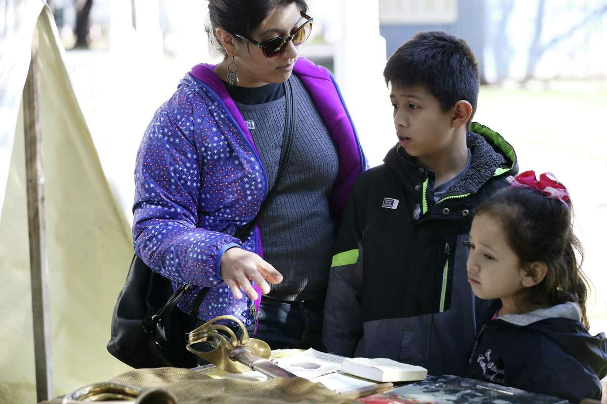 Ivonne Gutierrez looks over a display with her children, Julian, 9, and Elena, 4, during Buffalo Soldier Day at the University of Texas at San Antonio Institute of Texan Cultures, Sunday, Jan. 13, 2019. The event was part of DreamWeek.