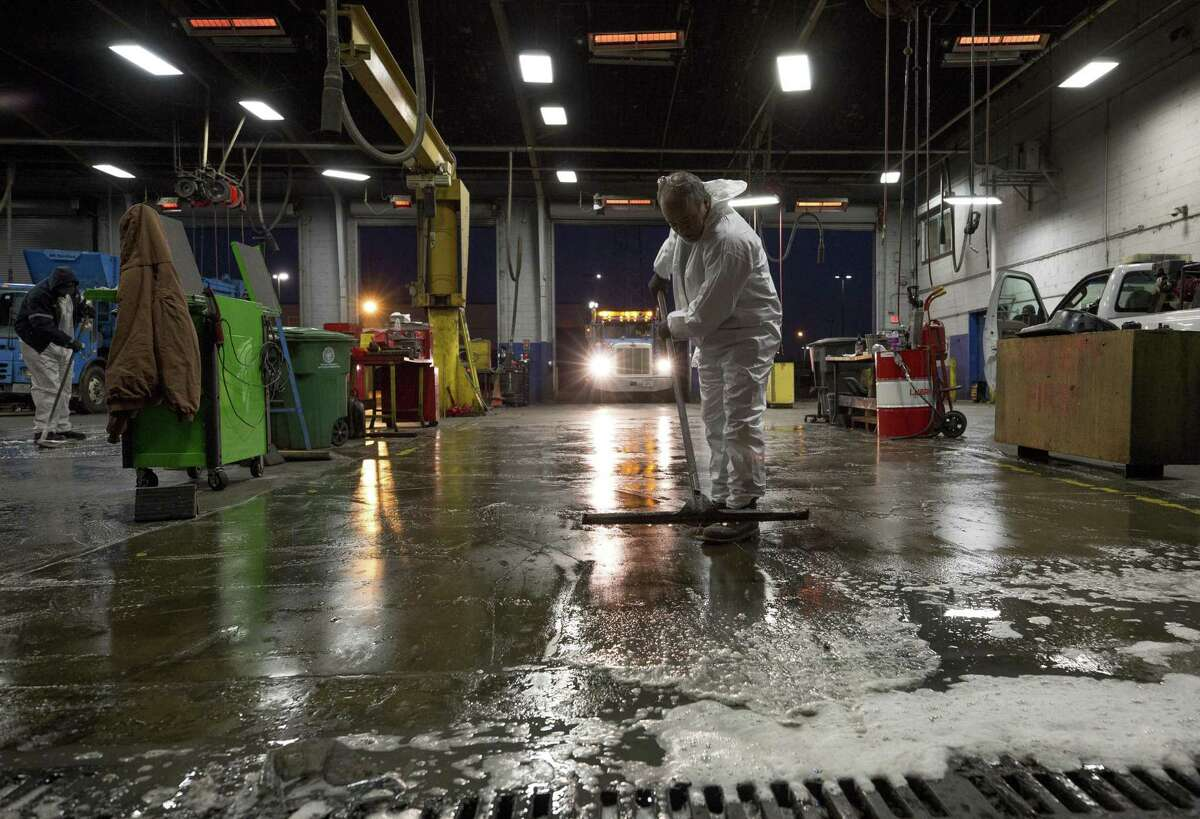 Mechanics with the city's Solid Waste Management Department wash the garage floor as they start their shift Friday, Jan. 4, 2019, in Houston. The department is struggling to compete with the salaries offered to drivers and mechanics are struggling in the private sector, therefore its is having difficulties filling the 20 to 25 mechanic spots open. This also makes keeping up with its aging fleet of automated garbage and recycling trucks on the streets challenging. Sixty nine new trucks should arrive this summer.