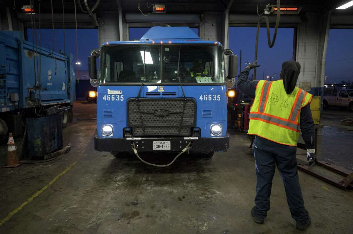 Tracy Kennard, 54, a mechanic for the city's Waste Management Department, waves into the garage the first of many garbage trucks that need maintenance.