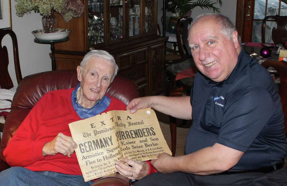 Dick Wood, left, a retired WTEN-TV News anchor and Army veteran, presents a 100-year-old copy of The Providence Daily Journal to Gene Loparco in Wood?s Latham home. The newspaper leads with stories marking the end of World War I. (Linda Loparco)