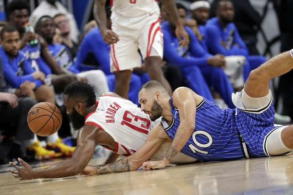 Houston Rockets' James Harden, left, and Orlando Magic's Evan Fournier go after a loose ball during the second half of an NBA basketball game, Sunday, Jan. 13, 2019, in Orlando, Fla. (AP Photo/John Raoux)