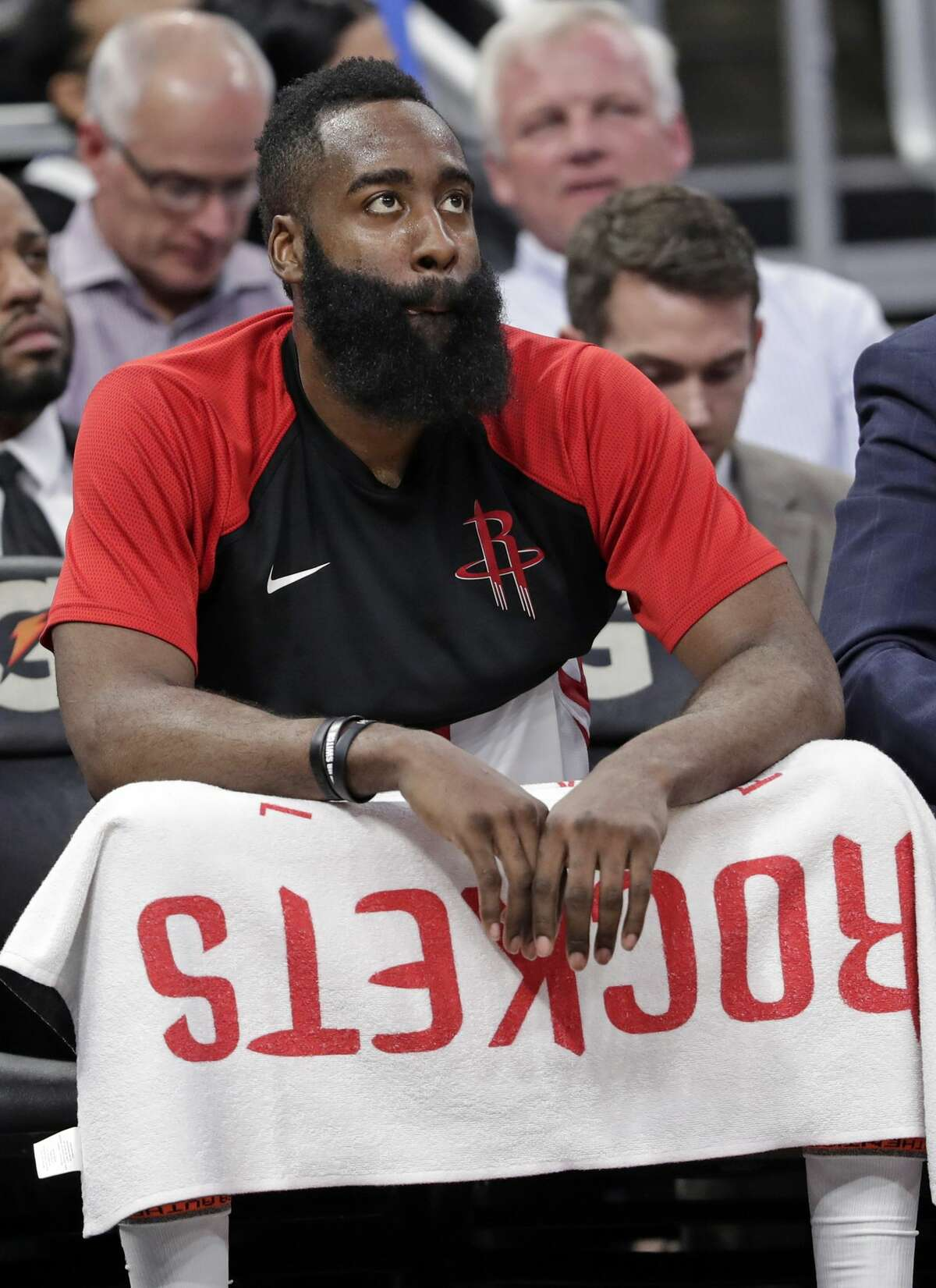 Houston Rockets' James Harden watches his teammates on the court against the Orlando Magic as he takes a breather on the bench during the second half of an NBA basketball game, Sunday, Jan. 13, 2019, in Orlando, Fla. (AP Photo/John Raoux)
