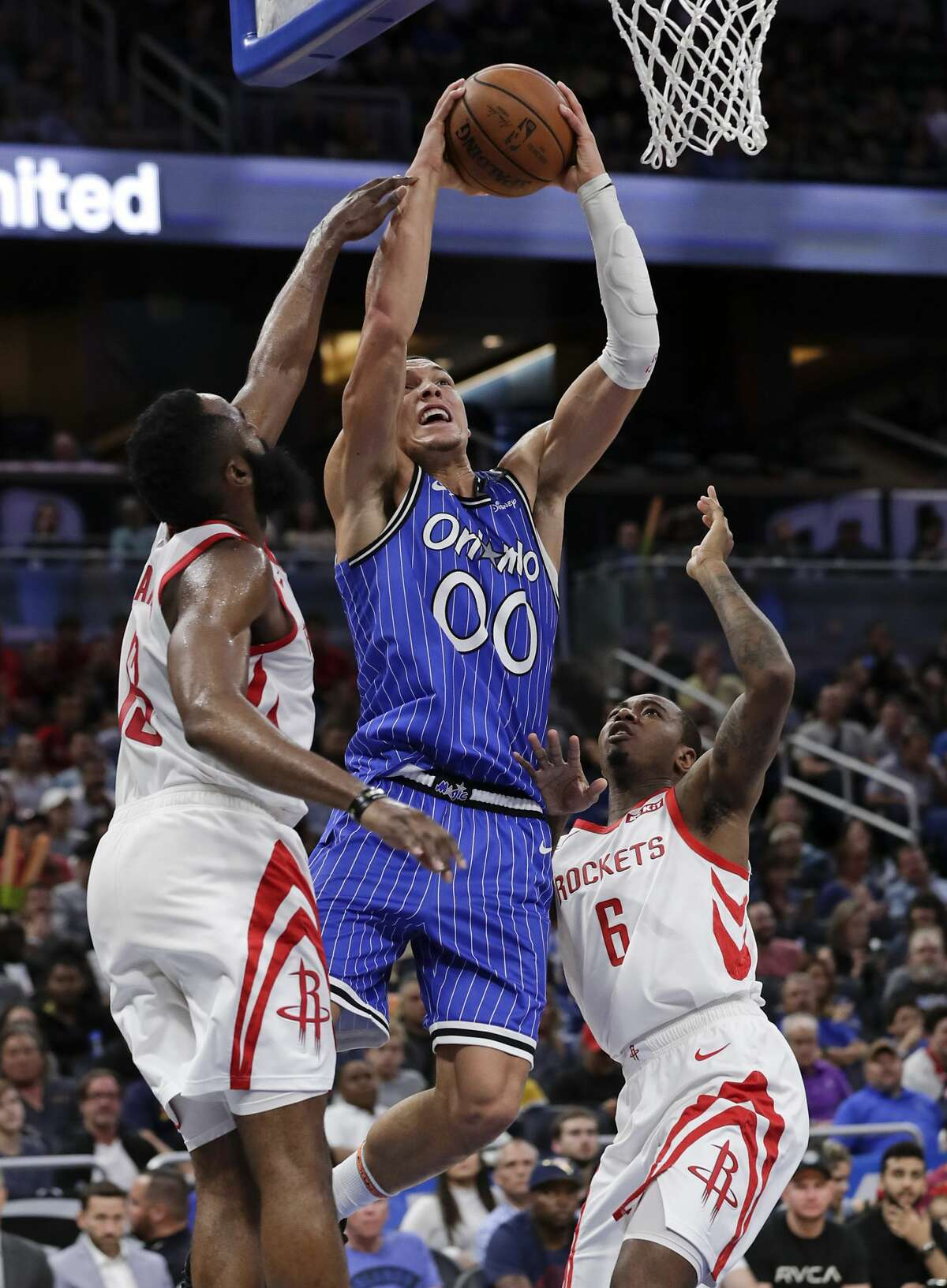 Orlando Magic's Aaron Gordon (00) shoots as he gets between Houston Rockets' James Harden, left, and Gary Clark (6) during the second half of an NBA basketball game, Sunday, Jan. 13, 2019, in Orlando, Fla. (AP Photo/John Raoux)