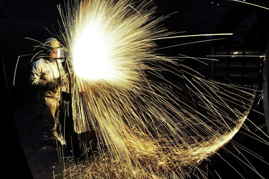 (FILES) This file photo taken on January 17, 2018 shows a worker cutting steel in Qingdao in China's eastern Shandong province.  China opened trade in iron ore futures to foreign investors on May 4, 2018 on the market of the north-eastern city of Dalian, aiming to boost its pricing clout for one of its top imports, in one additional signal of opening up amidst a trade row with the US. / AFP PHOTO / - / China OUT-/AFP/Getty Images Photo: - / AFP or licensors