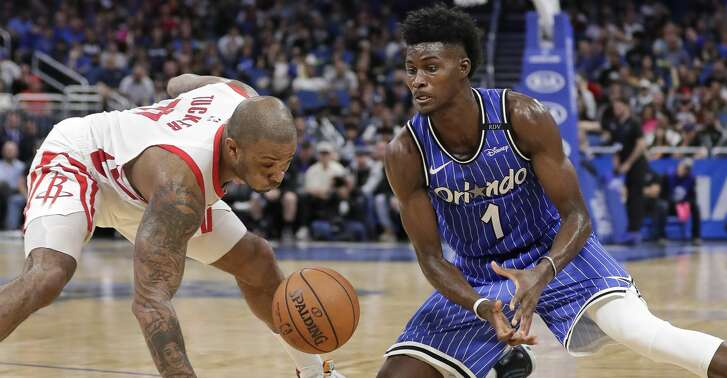 Houston Rockets' P.J. Tucker, left, and Orlando Magic's Jonathan Isaac (1) go after a loose ball during the second half of an NBA basketball game, Sunday, Jan. 13, 2019, in Orlando, Fla. (AP Photo/John Raoux)