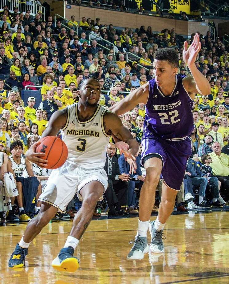Michigan guard Zavier Simpson (3) drives toward the basket, defended by Northwestern forward Pete Nance (22) in the second half of an NCAA college basketball game in Ann Arbor, Mich., Sunday, Jan. 13, 2019. Michigan won 80-60. (AP Photo/Tony Ding) Photo: Tony Ding / Copyright 2019 The Associated Press. All rights reserved