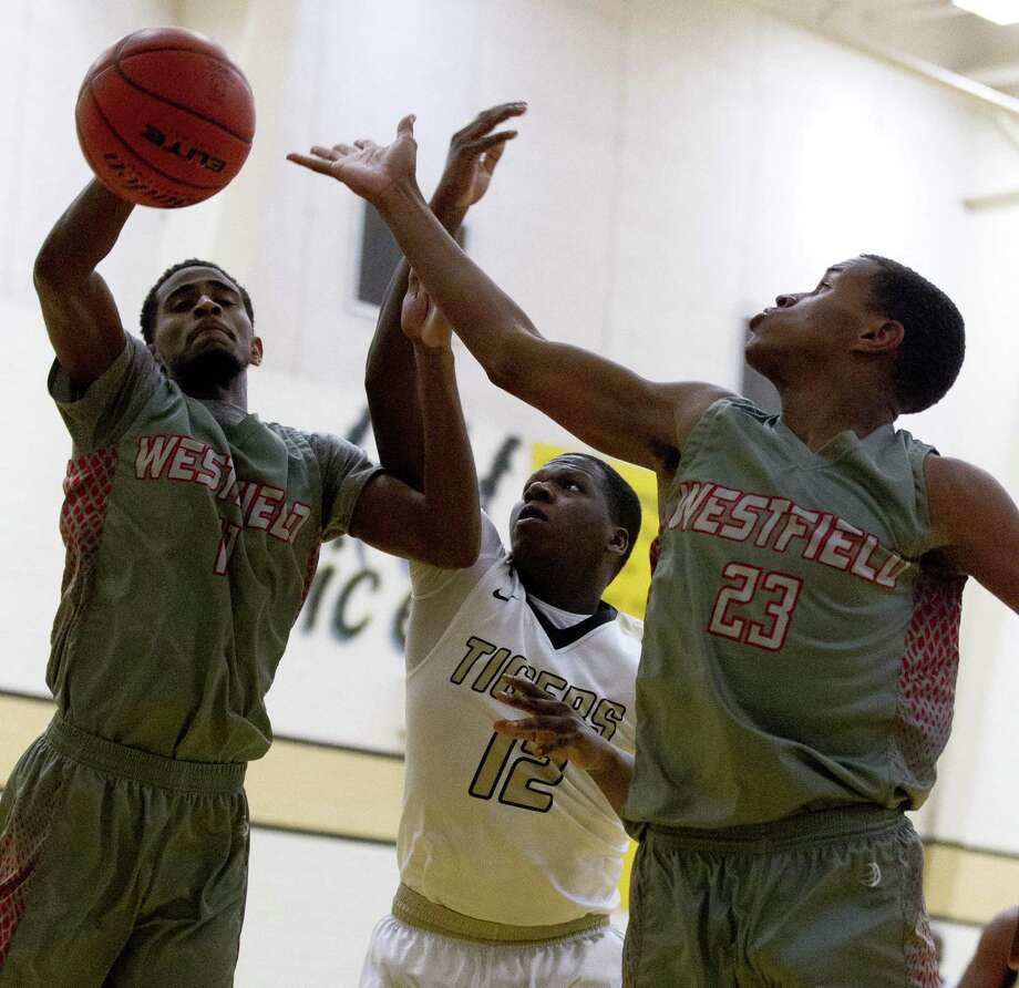 Conroe guard Bryce Harris (12) goes for a rebound against Westfield forward Dylan McCray (11) and forward Willie Williams (23) during the third quarter of a non-district high school basketball game at Conroe High School, Tuesday, Dec. 4, 2018, in Conroe. Photo: Jason Fochtman, Houston Chronicle / Staff Photographer / © 2018 Houston Chronicle