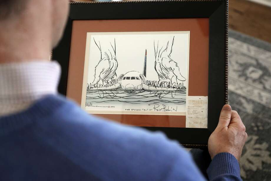 Steve O'Brien holds a drawing framed with his boarding pass from the Jan. 15, 2009, flight that landed in the Hudson River. Photo: Chuck Burton / Associated Press