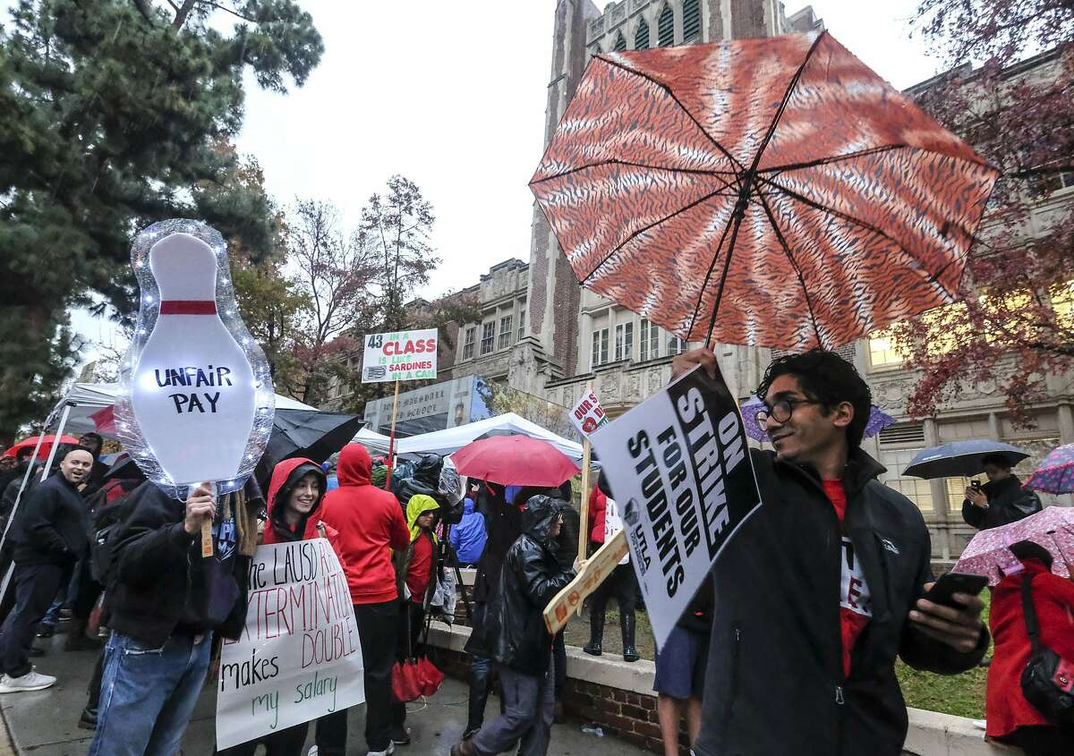 Teachers strike in the rain outside John Marshall High School, Monday, Jan. 14, 2019, in Los Angeles. Tens of thousands of Los Angeles teachers are striking after contentious contract negotiations failed in the nation's second-largest school district.(AP Photo/Ringo H.W. Chiu)