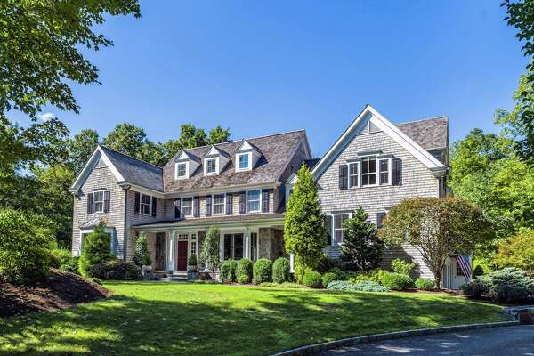 The natural-colored colonial house at 97 Whipstick Road has 14 rooms of modern amenities inside and a wealth of recreational features inside and out.