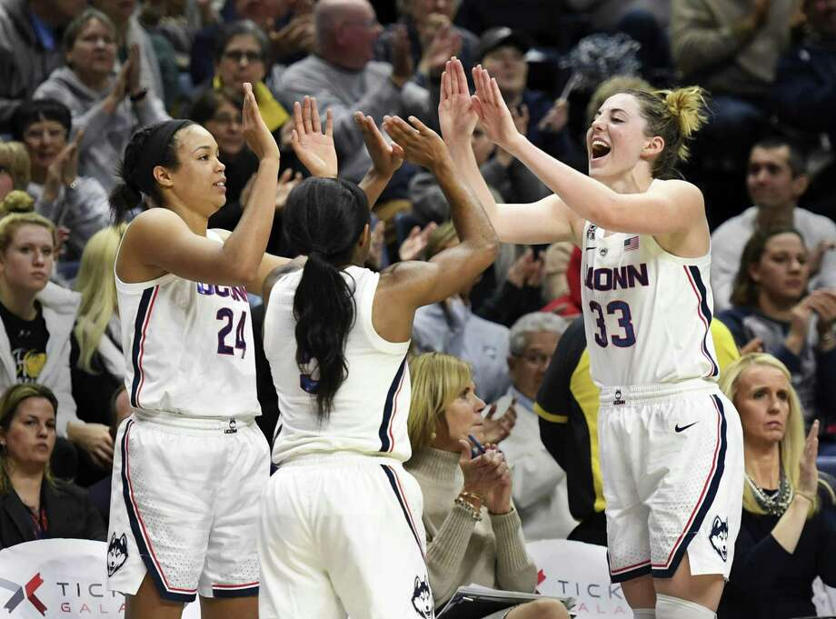 UConn's Napheesa Collier (24), Crystal Dangerfield (5) and Katie Lou Samuelson (33) celebrate after Sunday's win over South Florida. Photo: Stephen Dunn / Associated Press / Copyright 2019 The Associated Press. All rights reserved