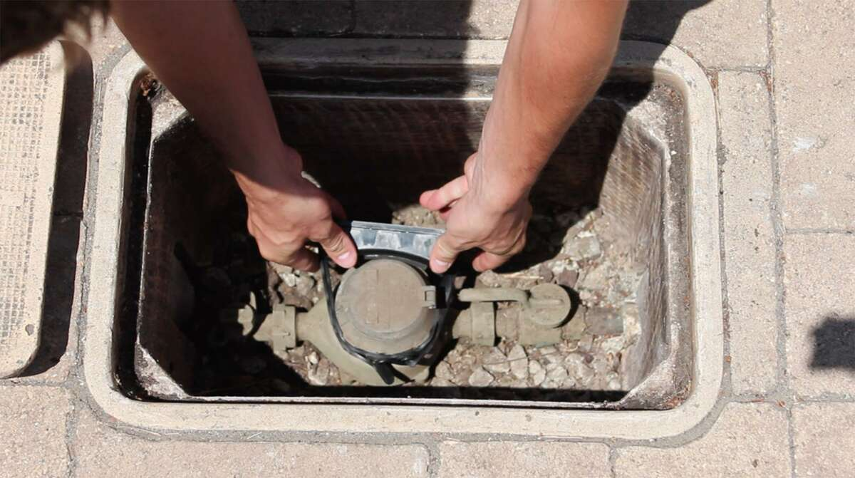 A Flume water sensor is shown being installed on an underground water meter to track water use and detect leaks. SAWS is pilot testing the product with about 500 customers.