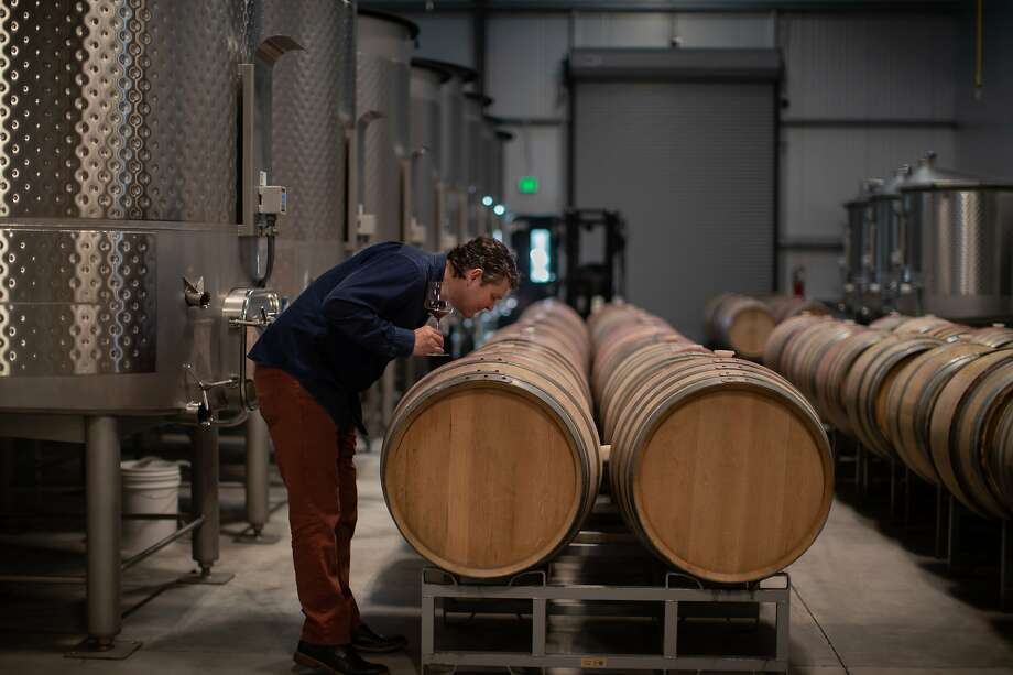 Kyle Evans checks out a wine barrel at Grand Cru Custom Crush in Windsor, which is reopening this weekend for visitors. Photo: Paul Kuroda / Special To The Chronicle 2019