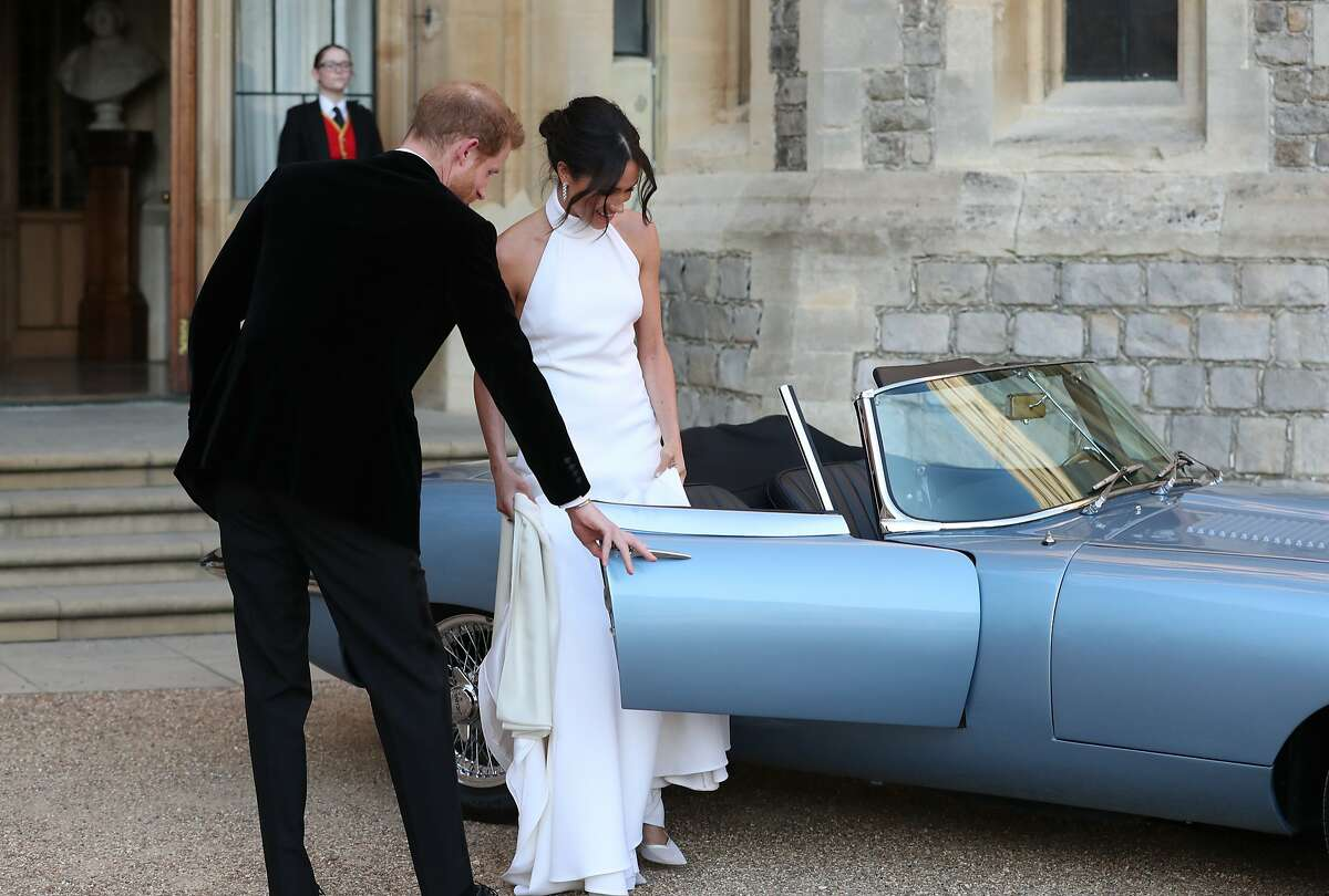 WINDSOR, UNITED KINGDOM - MAY 19: Prince Harry, Duke of Sussex helps his new bride the Duchess of Sussex into the car as they leave Windsor Castle after their wedding to attend an evening reception at Frogmore House, hosted by the Prince of Wales on May 19, 2018 in Windsor, England.