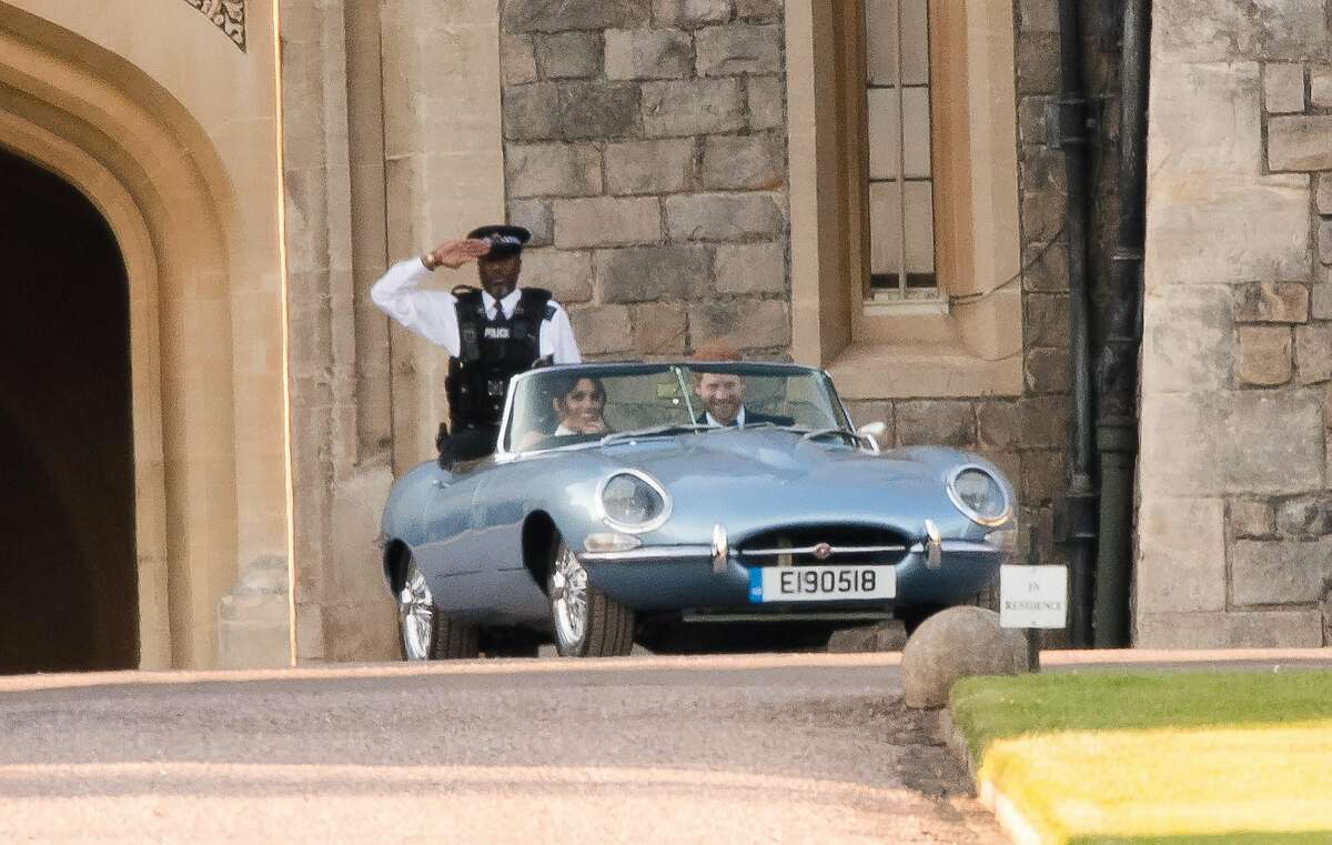 WINDSOR, ENGLAND - MAY 19: Prince Harry, Duke of Sussex, and Meghan Markle, Duchess of Sussex, leave Windsor Castle in Windsor on May 19, 2018 in an E-Type Jaguar after their wedding to attend an evening reception at Frogmore House.