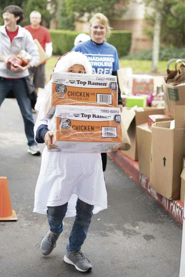 A youngster helps carry food at the Montgomery County Food Bank Holiday Food Drive in December. The Food Bank collected 56,629 pounds of food during the Holiday Food Drive.