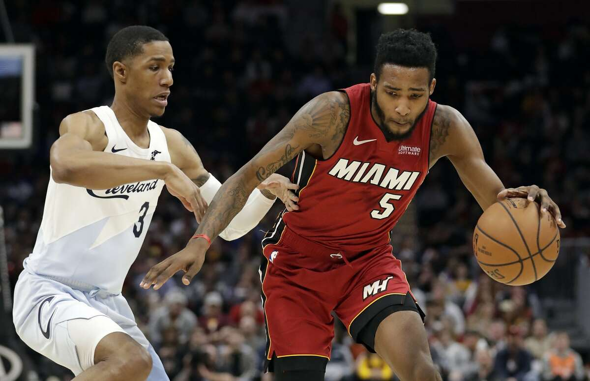 Miami Heat's Derrick Jones Jr. (5) drives past Cleveland Cavaliers' Patrick McCaw (3) in the second half of an NBA basketball game, Wednesday, Jan. 2, 2019, in Cleveland. Miami won 117-92. (AP Photo/Tony Dejak)