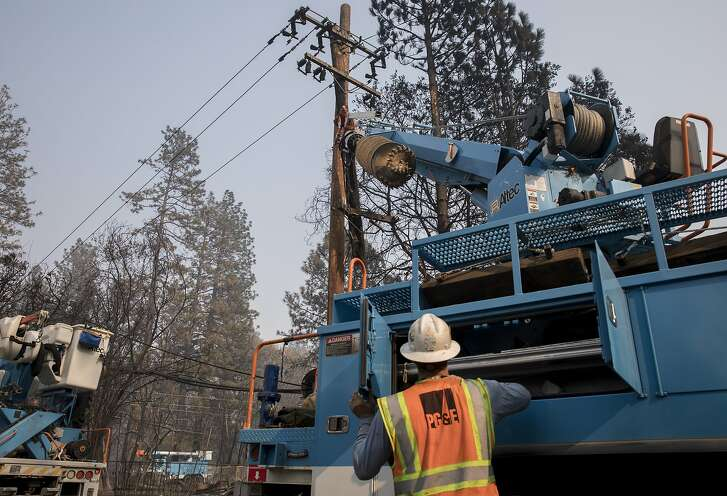 PG&E crews work to clear downed power lines and telephone poles in Paradise, Calif. Saturday, Nov. 17, 2018 after the Camp Fire ripped through the entire town.