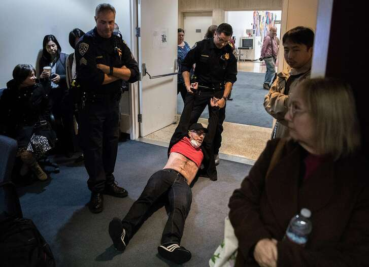 Craig Ostrin is dragged out by sheriff's deputies while protesting during a California Public Utilities Commission meeting San Francisco, Calif. Wednesday, Nov. 28, 2018 surrounding the fate of PG&E following multiple deadly wildfires.