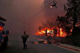 A PG&E worker runs while dealing with downed power lines during Camp Fire in Paradise, Calif.. on Thursday, November 8, 2018.
