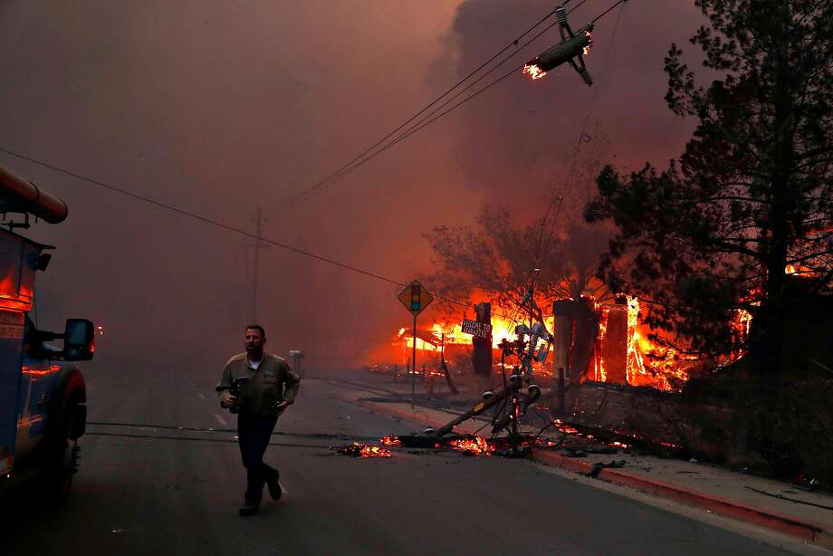 A PG&E worker runs while dealing with downed power lines during Camp Fire in Paradise, Calif.. on Thursday, November 8, 2018. Photo: Scott Strazzante / The Chronicle 2018