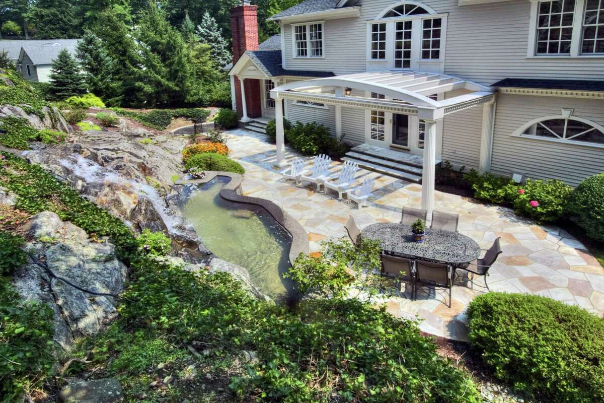 This property features a grand, man-made waterfall feature that spills into a pool on the Brazilian stone patio.