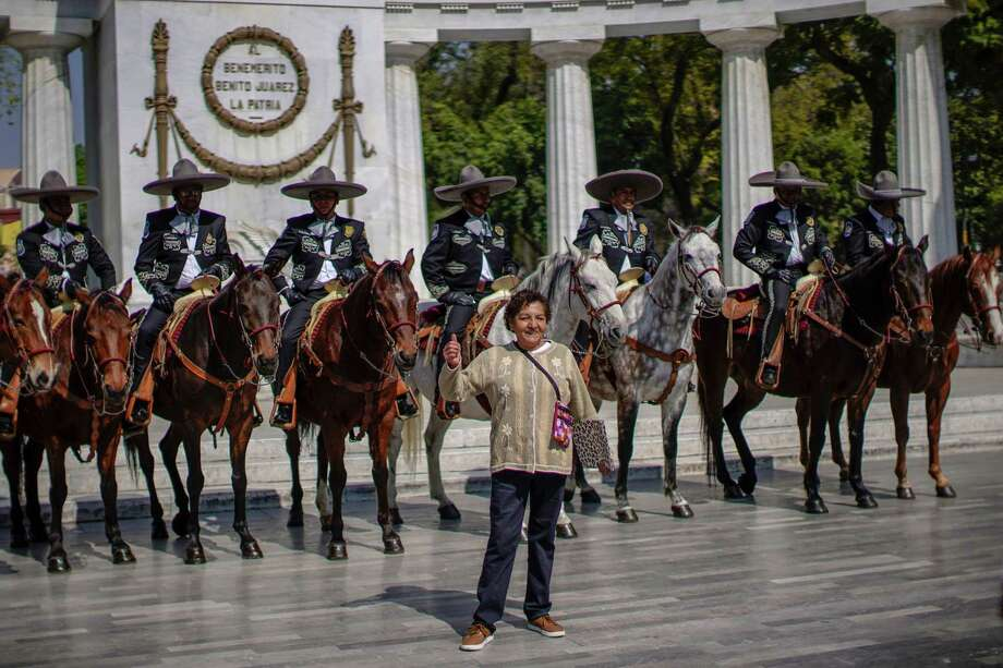 A woman poses for pictures in front of tourist police officers wearing Mexican charro outfits in the Alameda Central in Mexico City, on January 10, 2019. Photo: PEDRO PARDO / AFP /Getty Images / AFP or licensors