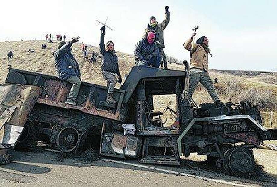 Protesters against the Dakota Access oil pipeline stand on a burned-out truck near Cannon Ball, North Dakota, in 2016. North Dakota officials, including Gov. Doug Burgum, want a federal judge to dismiss a civil rights lawsuit filed over a five-month shutdown of a portion of Highway 1806 during protests against the Dakota Access oil pipeline. Photo: James MacPherson | AP